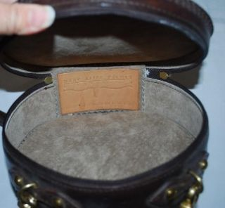 Mary Alice Parker round leather purse. It is dark brown with a tooled
