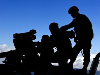 Silhouette of Soldiers Operating a BGM 71 Tow Guided Missile System Photographic Print by Stocktrek Images