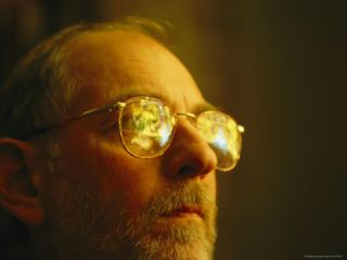 Man in Glasses with Stained Glass Windows Reflected in Them Photographic Print by Joel Sartore