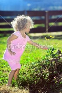 Cute little girl with blond curly hair picking flowers on green